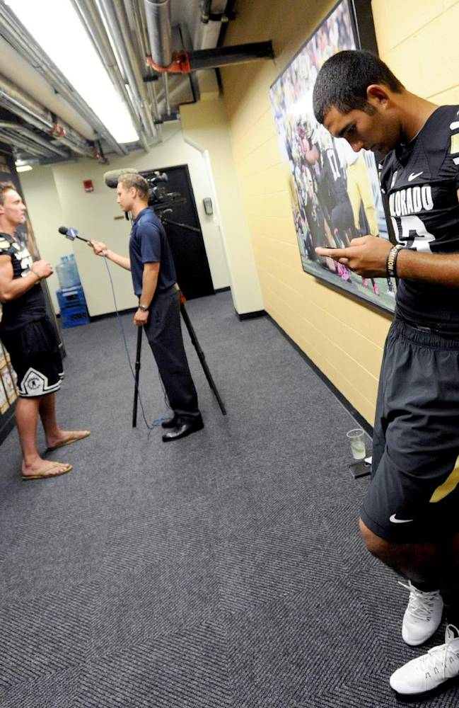 Colorado quarterback, Sefo Liufau, right, waits for Nelson Spruce to be interviewed during NCAA college football media day on Saturday, Aug. 9, 2014, in Boulder, Colo