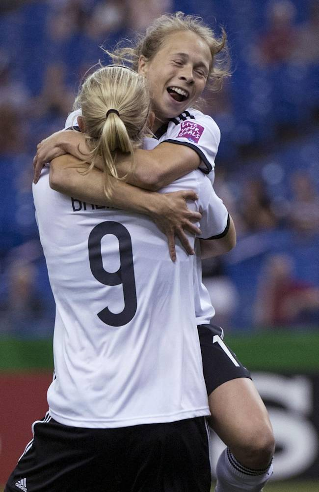 Germany's Theresa Panfil leaps into the arms of teammate Pauline Bremer following a goal by Bremer against France during the first half of a FIFA U-20 women's World Cup semifinal in Montreal on Wednesday, Aug. 20, 2014
