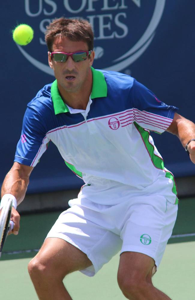 Tommy Robredo, of Spain, returns a volley to Sam Querrey at the Western & Southern Open tennis tournament, Wednesday Aug. 13, 2014, in Mason, Ohio