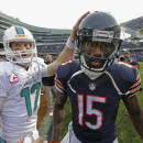 Miami Dolphins quarterback Ryan Tannehill (17) talks to Chicago Bears wide receiver Brandon Marshall (15) after their NFL football game Sunday, Oct. 19, 2014 in Chicago. The Dolphins won 27-14. (AP Photo/Charles Rex Arbogast)