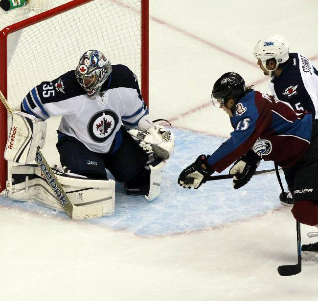 Winnipeg Jets goalie Al Montoya, left, makes a stick save of a shot by Colorado Avalanche right wing PA Parenteau, front right, as Jets defenseman Mark Stuart covers in the third period of the Avalanche's 3-2 victory in an NHL hockey game in Denver on Sunday, Oct. 27, 2013