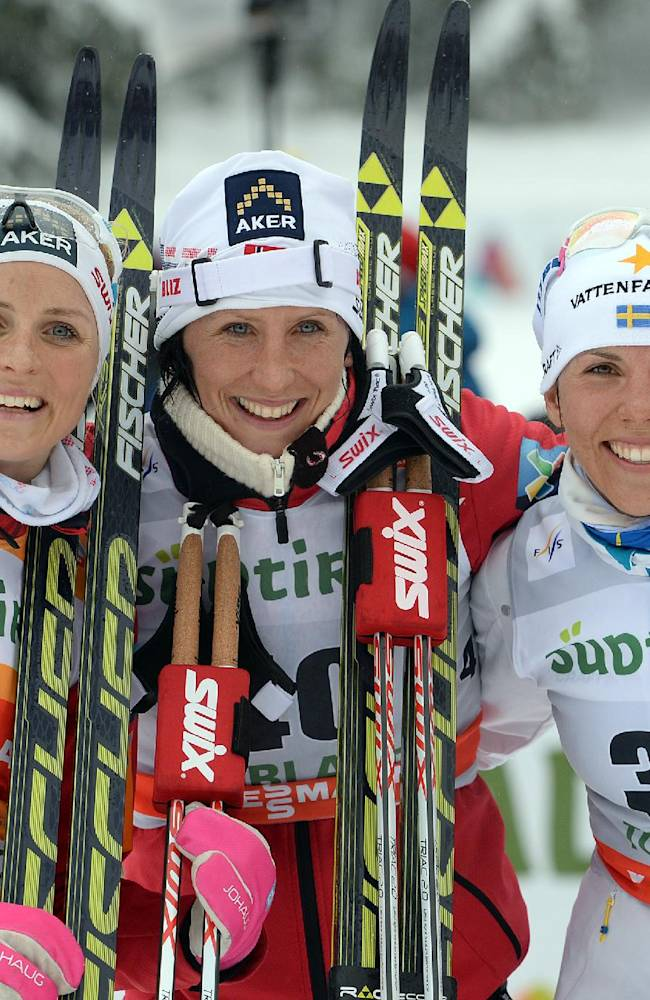 First placed Marit Bjoergen of Norway, center, poses for photographers as she celebrates on the podium of a cross country ski, women's World Cup, 10 kilometer classic race, flanked by second placed Therese Johaug of Norway, left, and third placed Charlotte Kalla of Sweden,  in Dobbiaco, Italy, Saturday Feb.1, 2014