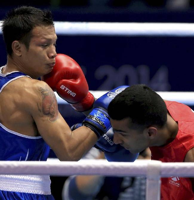 Scotland's Aqeel Ahmed, right,  trades blows with India's Devendro Laishram in the men's light flyweight  quarter-final at the Commonwealth Games Glasgow 2014, in Glasgow Scotland, Wednesday July 30, 2014