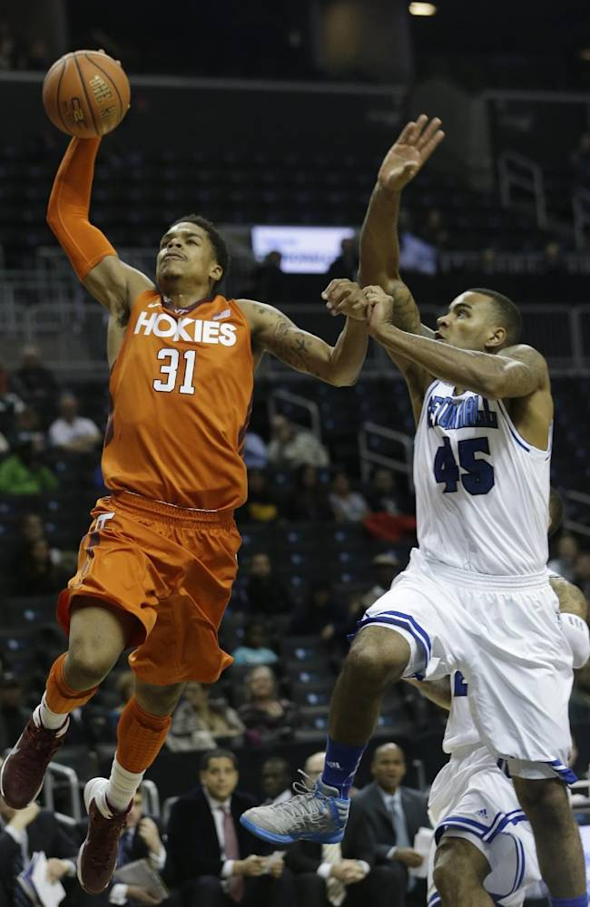 Virginia Tech's Jarell Eddie (31) drives past Seton Hall's Stephane Manga (45) during the first half of a consolation game in the Coaches vs. Cancer NCAA college basketball game on Saturday, Nov. 23, 2013, in New York. Manga blocked the shot on the play