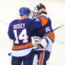 New York Islanders goalie Chad Johnson (30) and defenseman Thomas Hickey (14) celebrate after their NHL hockey game against the Carolina Hurricanes, Saturday, Oct. 11, 2014, in Uniondale, N.Y. The Islanders won 4-3 The Associated Press