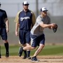 Milwaukee Brewers' Mark Reynolds, right, flips the ball to first base as teammates Lyle Overbay, left, and Hunter Morris both look on during Brewers spring training baseball practice, Thursday, Feb. 20, 2014, in Phoenix The Associated Press
