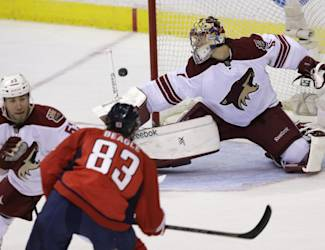 Phoenix Coyotes goalie Mike Smith (41) deflects the puck shot by Washington Capitals Jay Beagle (83) as Coyotes' Derek Morris (53) defends during the second period of an NHL hockey game, Saturday, March 8, 2014, in Washington. (AP Photo/Carolyn Kaster)