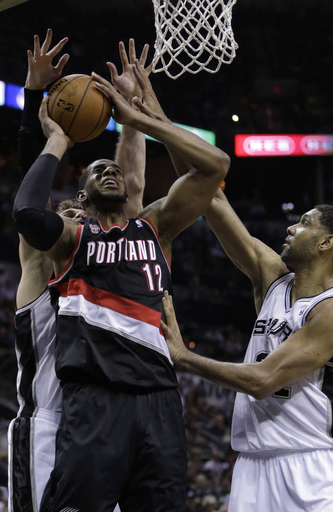 Portland Trail Blazers' LaMarcus Aldridge (12) is pressured by San Antonio Spurs' Tim Duncan, right, and Tiago Splitter during the second half of Game 2 of a Western Conference semifinal NBA basketball playoff series, Thursday, May 8, 2014, in San Antonio. San Antonio won 114-97