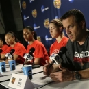 Louisville head coach Jeff Walz, right, and his players talk during a news conference for the women's NCAA Final Four college basketball tournament final, Monday, April 8, 2013, in New Orleans. Louisville plays Connecticut in the championship game on Tuesday. (AP Photo/Dave Martin)