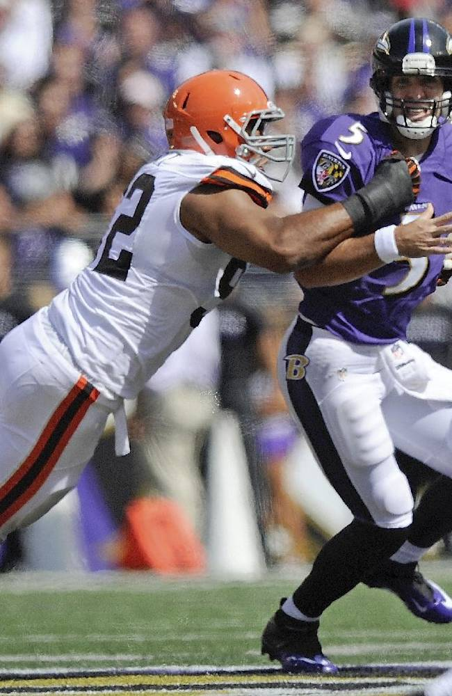 Baltimore Ravens quarterback Joe Flacco (5) is pulled down by Cleveland Browns defensive end Desmond Bryant, left, during the first half of an NFL football game in Baltimore, Md., Sunday, Sept. 15, 2013