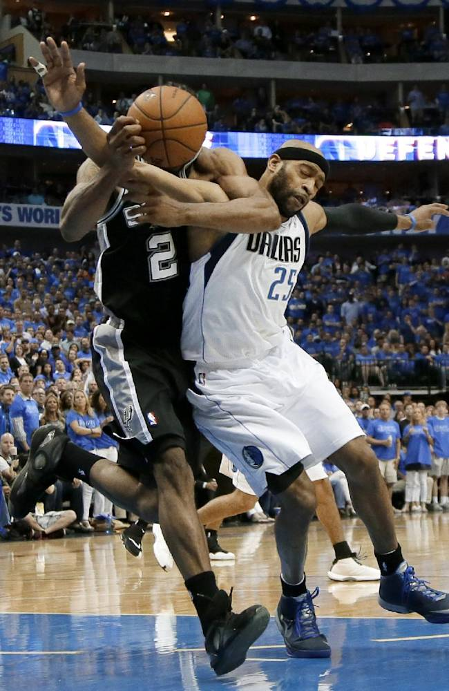 Dallas Mavericks' Vince Carter (25) gets tangled up with San Antonio Spurs' Kawhi Leonard (2) as they chase a rebound in the second half of Game 4 of an NBA basketball first-round playoff series, Monday, April 28, 2014, in Dallas. Carter was charged with a foul on the play. The Spurs won 93-89