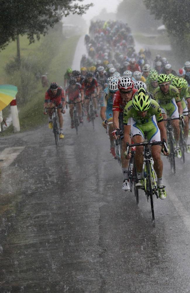 The pack rides in a downpour during the nineteenth stage of the Tour de France cycling race over 208.5 kilometers (129.6 miles) with start in Maubourguet and finish in Bergerac, France, Friday, July 25, 2014