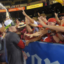 Los Angeles Angels' Mike Trout celebrates with fans after they clinched the American League division following their baseball game against the Seattle Mariners, Wednesday Sept. 17, 2014, in Anaheim, Calif. (AP Photo/Mark J. Terrill)