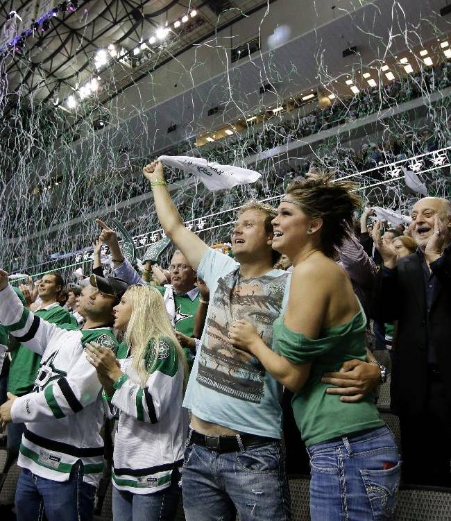 Fans celebrate as the horn sounds at the end of the third period of Game 3 of a first-round NHL hockey Stanley Cup playoff series game between the Anaheim Ducks and Dallas Stars, Monday, April 21, 2014, in Dallas. The Stars won 3-0