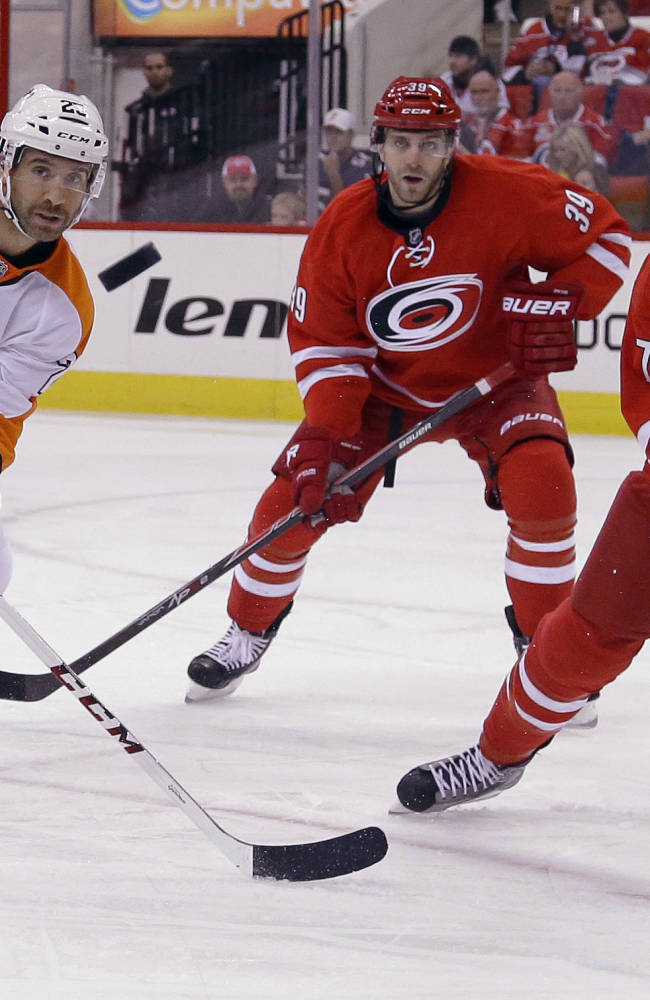 Philadelphia Flyers' Maxime Talbot (25) passes as Carolina Hurricanes' Patrick Dwyer (39) and Ryan Murphy (7) keep an eye on the puck during the first period of an NHL hockey game in Raleigh, N.C., Sunday, Oct. 6, 2013