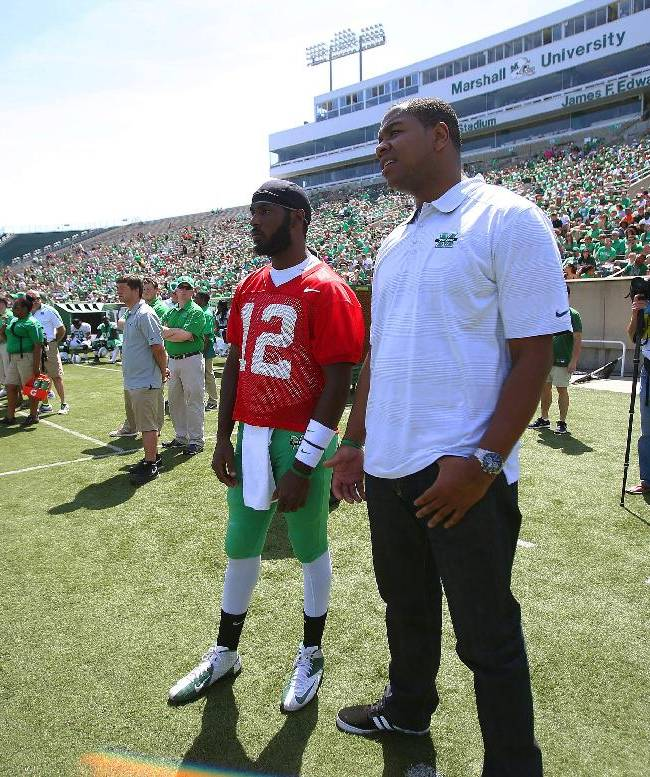 Senior quarterback Rakeem Cato (12) watches a play with former quarterback Byron Leftwich during the team's annual Green and White NCAA college football spring game Saturday, April 26, 2014, at Joan C. Edwards Stadium in Huntington, W.Va