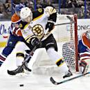 Boston Bruins Nick Johnson (32) and Edmonton Oilers Justin Schultz (19) battle for the puck as goalie Devan Dubnyk (40) looks for the puck during the first period of an NHL hockey game, Thursday, Dec. 12, 2013 in Edmonton, Alberta. (AP Photo/The Canadian Press, Jason Franson)