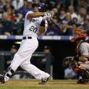 Colorado Rockies' Wilin Rosario, left, follows the flight of his two-run home run with San Francisco Giants catcher Buster Posey in the fifth inning of a baseball game in Denver, Saturday, May 18, 2013. (AP Photo/David Zalubowski)
