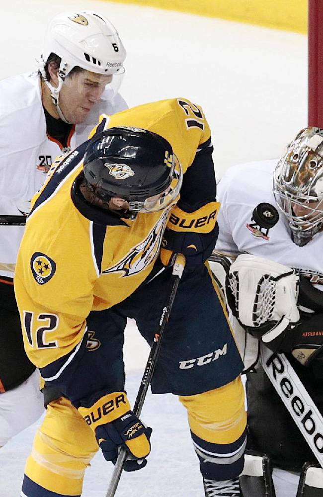 Anaheim Ducks goalie Frederik Andersen (31), of Denmark, reaches for the puck as Ben Lovejoy (6) tries to clear Nashville Predators forward Mike Fisher (12) out of the way in the first period of an NHL hockey game Thursday, Jan. 9, 2014, in Nashville, Tenn