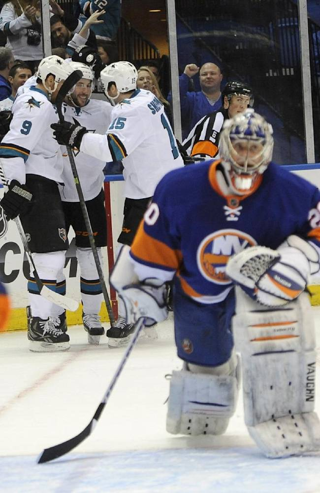 New York Islanders goalie Evgeni Nabokov (20) reacts as  San Jose Sharks' Martin Havlat (9), Jason Demers (5) and James Sheppard (15) celebrate Demers' goal in the first period of an NHL hockey game on Friday, March 14, 2014, in Uniondale, N.Y
