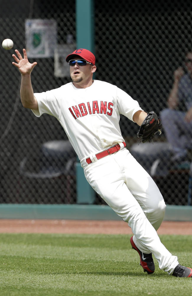 Cleveland Indians' Ryan Raburn bare hands the ball hit by Seattle Mariners' Brendan Ryan in the seventh inning of a baseball game, Monday, May 20, 2013, in Cleveland. Ryan was safe at first base.  (AP Photo/Tony Dejak)