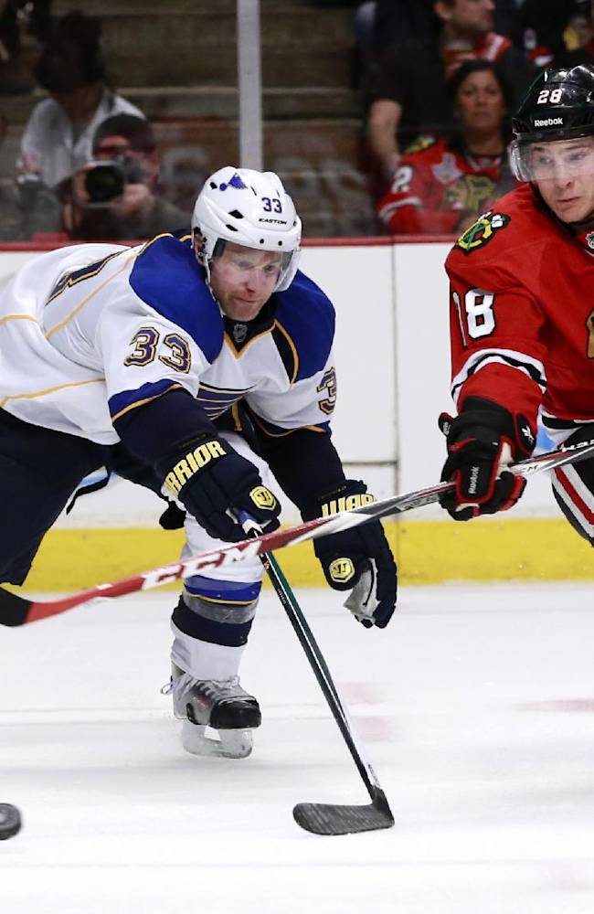 Chicago Blackhawks right wing Ben Smith (28) takes a backhanded shot on goal past St. Louis Blues defenseman Jordan Leopold during the second period in Game 3 of a first-round NHL hockey Stanley Cup playoff series game Monday, April 21, 2014, in Chicago