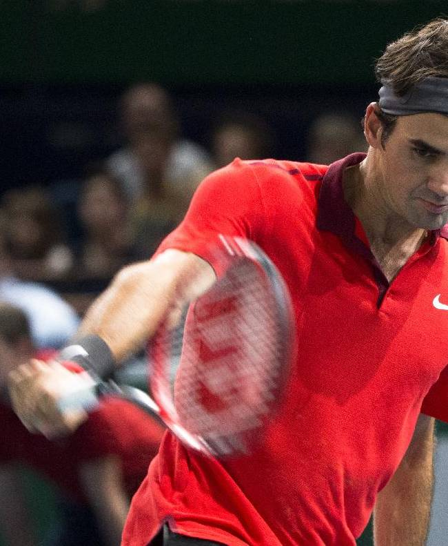 Roger Federer of Switzerland returns the ball  to France's Lucas Pouille during their third round match at the ATP World Tour Masters tennis tournament at Bercy stadium in Paris, France, Thursday, Oct. 30, 2014