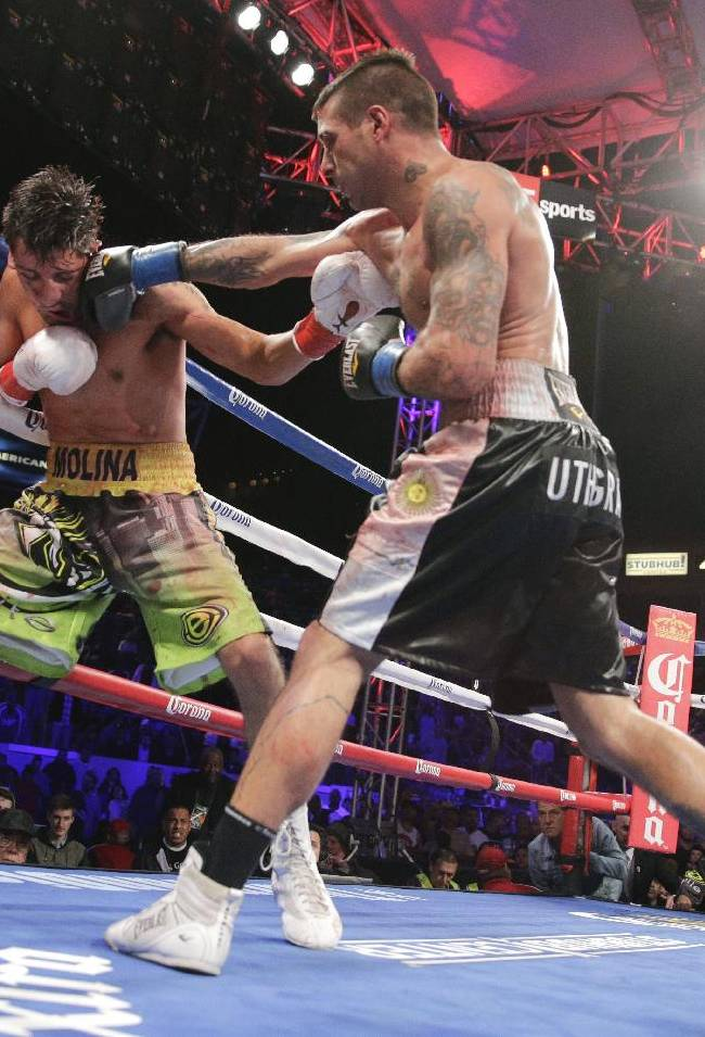 Lucas Matthysse, of Argentina, center, punches John Molina Jr. during the 11th round of a 140-pound boxing match on Saturday, April 26, 2014, in Carson, Calif. Matthysse won by knockout in the 11th round