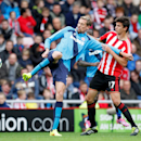 Stoke City's Peter Crouch, left, and Sunderland's Santiago Vergini challenge during their English Premier League soccer match at the Stadium of Light, Sunderland, England, Saturday, Oct. 4, 2014