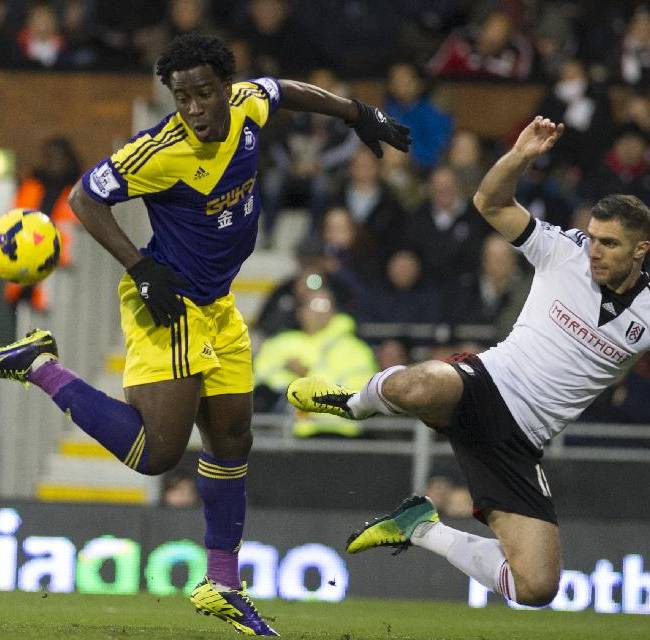 Fulham's Aaron Hughes, fights for the ball with Swansea City's Wilfried Bony, during their English Premier League soccer match, at the Craven Cottage stadium in London, Saturday, Nov. 23, 2013
