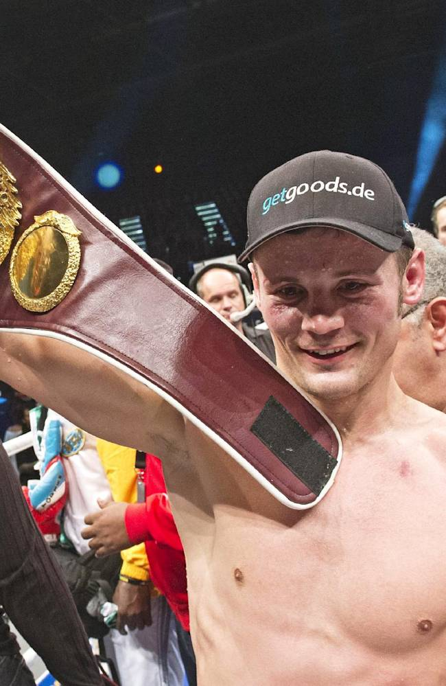 Robert Stieglitz of Germany holds up the title belt after winning his WBO Super Middleweight Championship bout against Isaac Ekpo of Nigeria in Leipzig, central Germany, Saturday, Oct. 19, 2013. Stieglitz retained his title