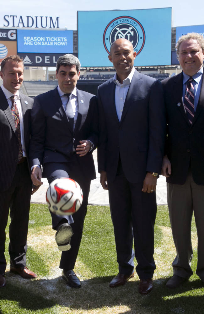 New York City Football Club soccer Chief Business Officer Tim Pernetti, head coach Jason Kreis, Director of Football Operations Claudio Reyna, retired New York Yankees pitcher Mariano Rivera, Yankees President Randy Levine, and Yankees COO Lonn Trost, left to right, pose for photos on the field at New York's Yankee Stadium, Monday, April 21, 2014. The Yankees announced that Yankee Stadium will serve as the Club's first home and begin play on March 2015