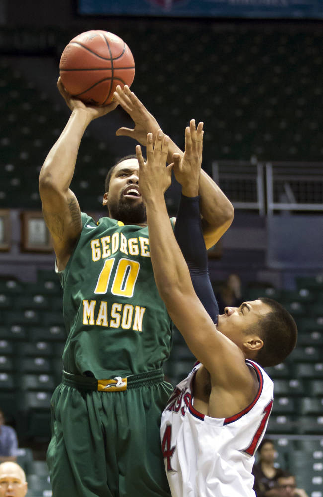 George Mason guard Sherrod Wright (10) shoots a jump shot while being defended by St. Mary's guard Stephen Holt (14) in the first half of an NCAA college basketball game at the Diamond Head Classic  Wednesday, Dec. 25, 2013, in Honolulu