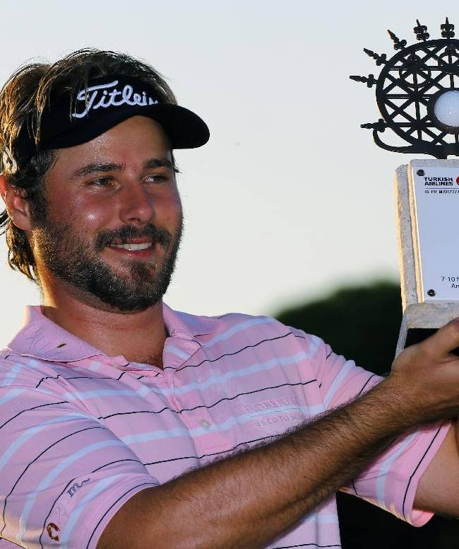 Victor Dubuisson of France smiles as he holds his trophy after winning the Turkish Open golf tournament at the Montgomerie Maxx Royal Course in Antalya, Turkey, Sunday, Nov. 10, 2013