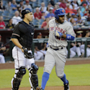 Arizona Diamondbacks catcher Miguel Montero, left, waits for the throw as New York Mets' Eric Young Jr. scores on a ground out by Lucas Duda during the first inning of the MLB National League baseball game on Tuesday, April 15, 2014, in Phoenix The Associ
