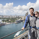 In this photo released by Destination NSW, Arizona Diamondbacks infielder Cliff Pennington poses with his wife after climbing the Sydney Harbour Bridge in Sydney. The Diamondbacks will play the Los Angeles Dodgers in their Major League Baseball season ope