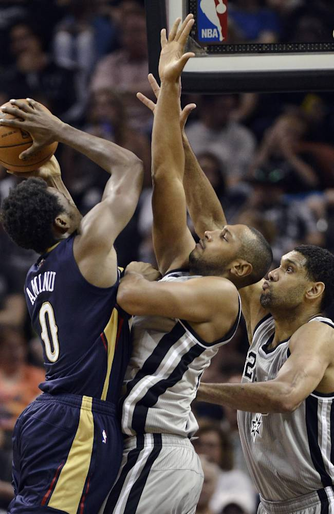 New Orleans Pelicans forward Al-Farouq Aminu, left, is defended by San Antonio Spurs forwards Boris Diaw, center, of France, and Tim Duncan during the second half of an NBA basketball game on Saturday, March 29, 2014, in San Antonio. San Antonio won 96-80