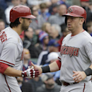 Arizona Diamondbacks' Cliff Pennington, right, celebrates with Mike Bolsinger after scoring on a double hit by Tony Campana during the second inning of a baseball game against the Chicago Cubs in Chicago, Thursday, April 24, 2014 The Associated Press