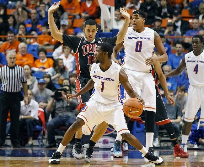 Boise State's Mikey Thompson (1) controls the ball against UNLV's Kendall Smith during the second half of an NCAA college basketball game in Boise, Idaho, on Saturday, Feb. 22, 2014. Boise State won 91-90 in overtime