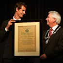 British tennis player Andy Murray, left, receives the Freedom of Stirling presented to him by Stirling Council Provost Mike Robbins during a special council meeting at his old school Dunblane High, in Dunblane, Scotland, Wednesday, April 23, 2014. Murray said he feels honored to receive the freedom of Stirling and an honorary degree from the university where he trained as a boy. (AP Photo/PA, Andrew Milligan)