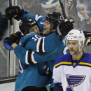 San Jose Sharks' Andrew Desjardins, left, celebrates with teammate Tye McGinn after scoring a goal against the St. Louis Blues during the second period of an NHL hockey game, Saturday, Dec. 20, 2014, in San Jose, Calif. In the foreground is Blues' Alex Pietrangelo. (AP Photo/George Nikitin)
