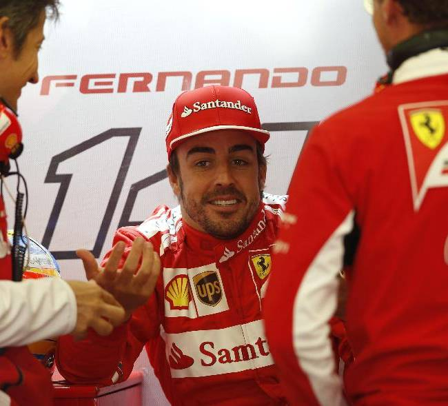 Ferrari driver Fernando Alonso of Spain talks with mechanics  the pit during the first free practice at the Spa-Francorchamps circuit, Belgium, Friday, Aug. 22, 2014. The Belgium Formula One Grand Prix will be held on Sunday