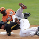 Baltimore Orioles second baseman Jemile Weeks, top, falls over Pittsburgh Pirates' Travis Ishikawa after throwing to first during the fifth inning of a spring exhibition baseball game in Bradenton, Fla., Monday, March 10, 2014 The Associated Press
