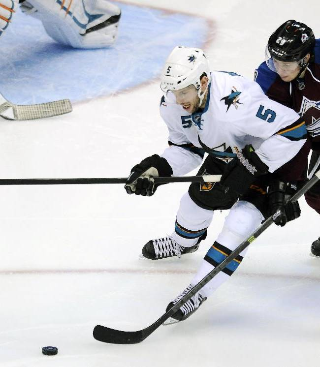 San Jose Sharks defenseman Jason Demers, left, and Colorado Avalanche center Nathan MacKinnon, right, fight for the puck in the third period of an NHL hockey game on Saturday, Jan. 4, 2014, in Denver. The Avalanche won 4-3