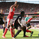 Liverpool's Sadio Mane, center, battles to hold off Arsenal's Theo Walcott, left, and Arsenal's Santi Cazorla, back, during the English Premier League soccer match between Arsenal and Liverpool at the Emirates Stadium in London, Sunday Aug. 14