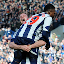 West Bromwich Albion's Chris Brunt lifts up goal scorer Stephane Sessegnon after he scored against Tottenham Hotspur during the English Premier League soccer match at The Hawthorns Stadium in West Bromwich, England, Saturday, April 12, 2014
