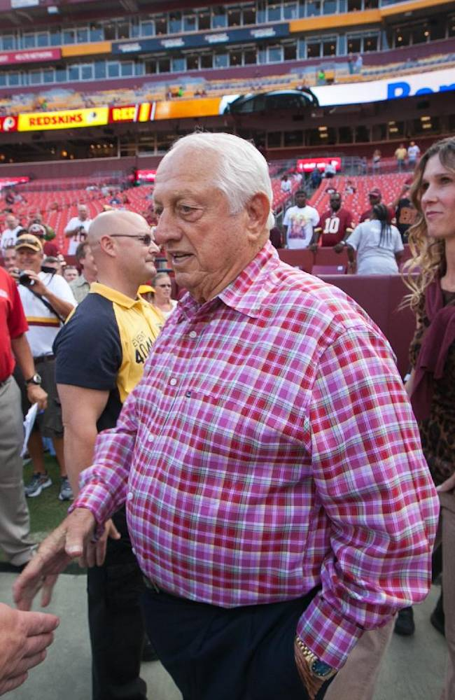 Former Los Angeles Dodgers baseball manager Tommy Lasorda, center ,is greeted by fans as he arrives on the field for their NFL football game between the Philadelphia Eagles and the Washington Redskins, Monday, Sept. 9, 2013, in Landover, Md