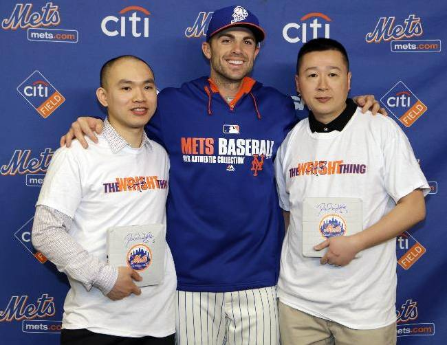 New York Police Department Police Officers James Li, left, and Randy Chow, right, pose for photographs with New York Mets' David Wright before a baseball game between the Mets and the Miami Marlins, Saturday, April 26, 2014, in New York. Li was shot once in each leg while chasing a suspect who entered a Brooklyn bus through the rear door