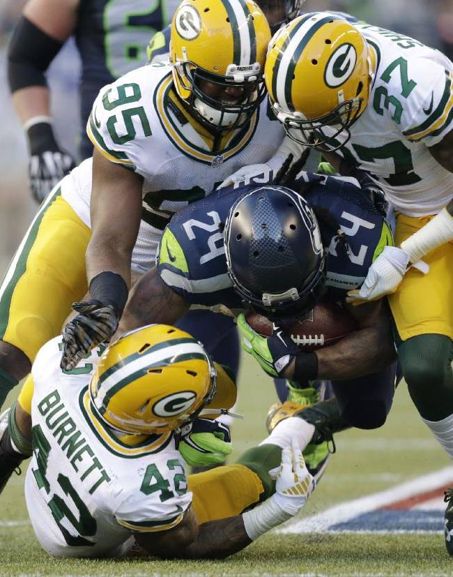 Seattle Seahawks running back Marshawn Lynch (24) is tackled by Green Bay Packers' Datone Jones (95), Sam Shields (37), and Morgan Burnett (42) as he rushes in the first half of an NFL football game, Thursday, Sept. 4, 2014, in Seattle