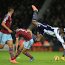 West Bromwich Albion's Victor Anichebe, second right, falls over after a challenge from West Ham United's James Tomkins, second left, during the English Premier League soccer match at The Hawthorns, West Bromwich, England, Tuesday Dec. 2, 2014